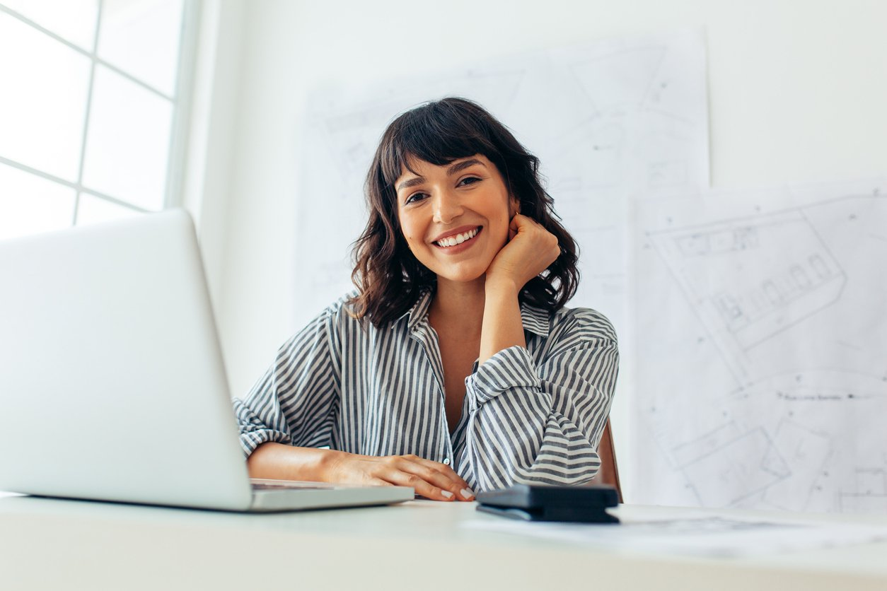 Person on laptop smiling   start up small business grants Fundid